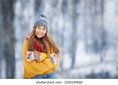 Winter young woman portrait. Beauty Joyful Model Girl laughing and having fun in winter park. Beautiful young female outdoors, Enjoying nature, wintertime