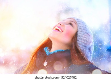 Winter young woman portrait. Beauty Joyful Model Girl raising hands, spinning and laughing, having fun in winter park. Beautiful young woman laughing outdoors. Enjoying nature, wintertime