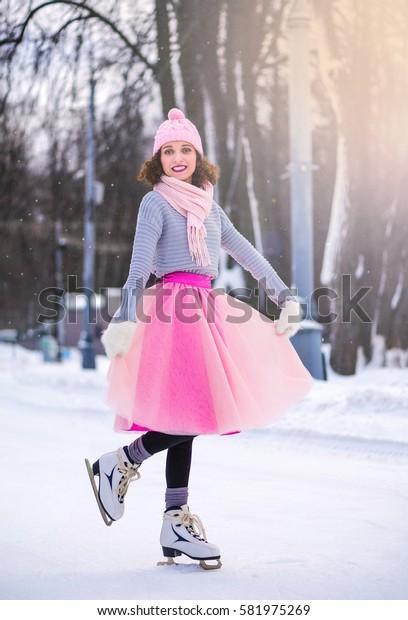 Winter young woman portrait with ice skates. Beauty Joyful Model Girl having fun in winter park. Enjoying nature, wintertime