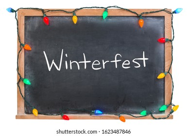 Winterfest written in white chalk on a black chalkboard surrounded with festive lightsisolated on white