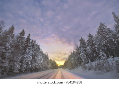 Winterroad in spruce forest at sunrise during a very clear cold morning. Sweden