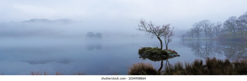 A winters day in the Lake District. Mist settles on Rydal Water surrounded by bare trees and mountains peaking out of the mist
