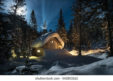 Winter's Tale. Wooden house with lightning windows and smoking chimneys in winter forest at moon night. Big snowdrifts are aroung the cottage. Fairytale view.