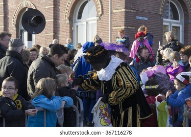 WINTERSWIJK, THE NETHERLANDS - 12 NOVEMBER 2011: Black Peter gives candy to the children on 12 November  2011 in Winterswijk, Holland.