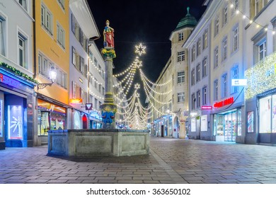 WINTERTHUR, SWITZERLAND - DECEMBER 26, 2015: Night scene of Marktgasse Street, with the Justitia Fountain, Christmas decorations, locals and visitors in Winterthur, Switzerland