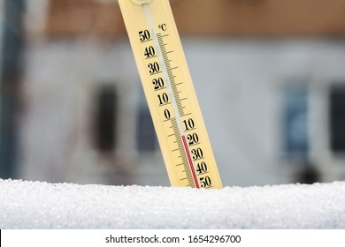 Wintertime. Thermometer in the snow shows very low temperatures against the background of a multi-storey building. Twelve degrees under zero celsius. Concept of weather forecast.