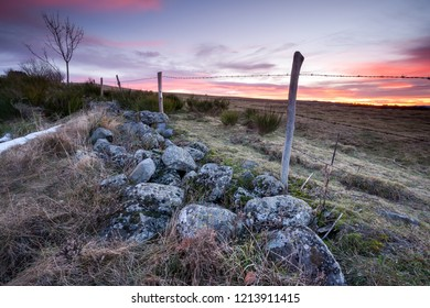 Wintery field at sunrise with stone boulders and old wooden fence with barbed wire Auvergne France