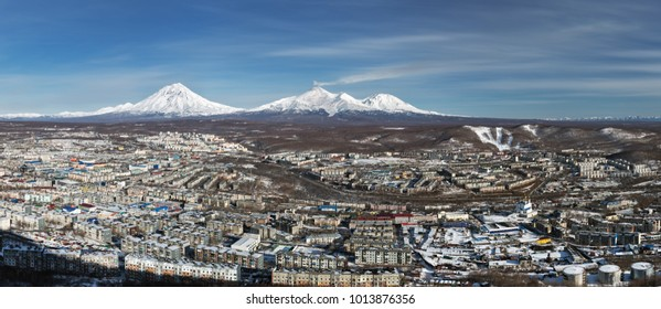 Wintery panorama of top view of urban landscape residential buildings of Petropavlovsk-Kamchatsky City and scenery volcanoes of Kamchatka Peninsula: Koryak Volcano, Avacha Volcano, Kozelsky Volcano.