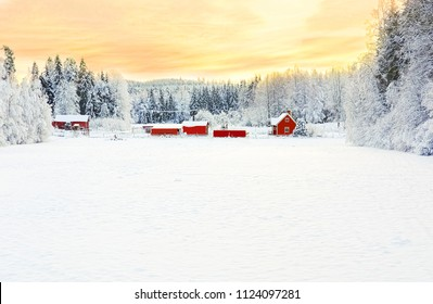 Wintery scene on a woodland homestead with stark contrast between the white snow, orange sunset, and red houses.