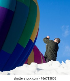 Winthrop, WA / USA - March 4, 2017: Man taking photos of hot air balloon inflating and getting ready to take off during Winthrop Balloon Festival