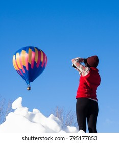 Winthrop, WA / USA - March 4, 2017: Woman taking photos of hot air balloon taking off at Winthrop Balloon Festival