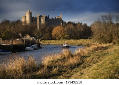 Wintry afternoon sunshine illuminates Arundel Castle and the River Arun in West Sussex, England.
