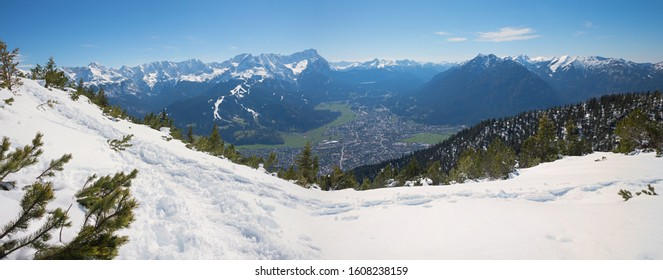wintry hiking path at Wank mountain, view to Zugspitze and tourist resort Garmisch-Partenkirchen, upper bavaria