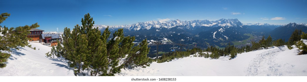 wintry landscape at Wank mountain, view to Zugspitze and tourist resort Garmisch-Partenkirchen, wooden alp hut at the summit