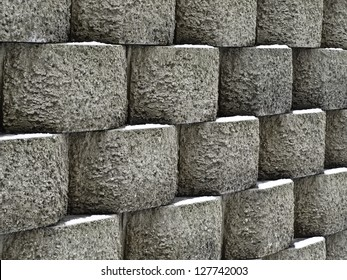 Wintry pattern of architecture and nature: Retaining wall of textured concrete blocks with snow in the same spot on each
