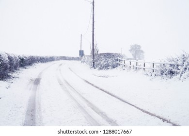 Wintry scene of lane from Hatton Bank to Hampton Lucy in Warwickshire, UK in a blizzard and covered with snow.