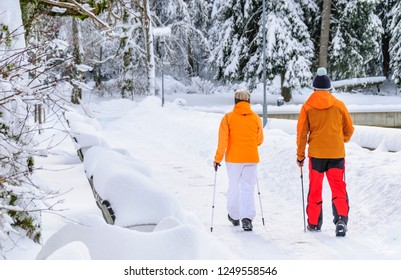 wintry tour with nordic walking sticks in park
