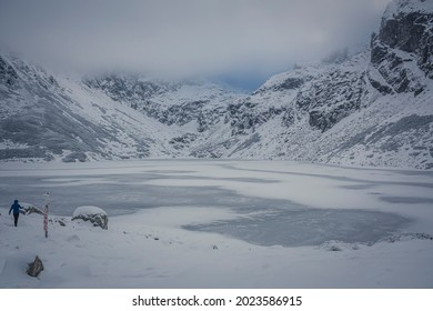 Wintry tranquility in Tatra Mountains, Poland. Single hiker near Czarny Staw Gąsienicowy Lake. Clouds above high peaks. Selective focus on the rocks, blurred background. - Shutterstock ID 2023586915