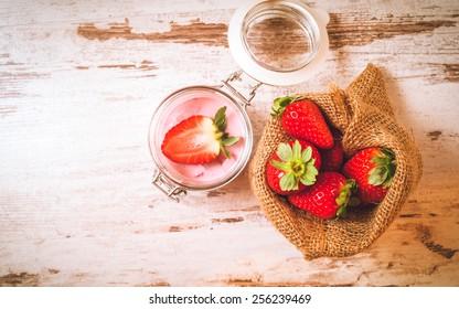 Wiosenne owoce, truskawki w lnianym worku z truskawkowym jogurtem na vintage drewnianym stole. - Shutterstock ID 256239469