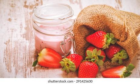 Wiosenne owoce, truskawki w lnianym worku z truskawkowym jogurtem na vintage drewnianym stole. - Shutterstock ID 291425630