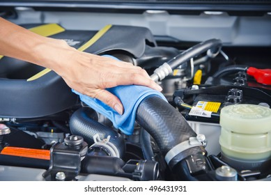 Wipe cleaning the car engine with blue microfiber cloth