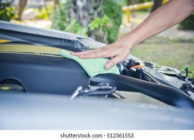Wipe cleaning the car engine with green microfiber cloth