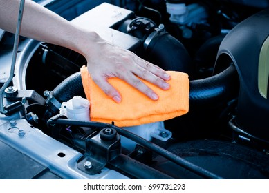 Wipe cleaning the car engine with orange microfiber cloth