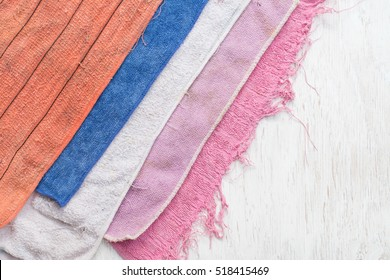 Wipe the cleaning towel,Hand with old green cleaning rag on wood background.