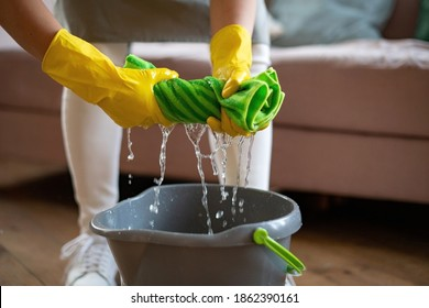 A wiper in rubber gloves wrung out a green rag. Professional cleaning service. Cleaning floors with a mop. Squeezing, twisted rag