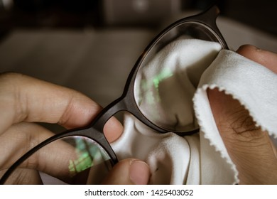 wiping glasses with microfiber cloth