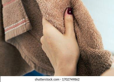 Wiping hands with a towel. The concept of care for cleanliness, personal hygiene. Disease prevention. The woman wipes his hands after washing them