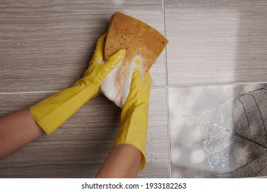 wiping the wall with a yellow sponge in yellow gloves