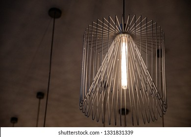 Wire chandelier closeup. Modern metal lampshade. Lamp with long glass light bulb inside. Abstract textured background. Geometric line shapes. Minimal backdrop. Interior decoration. Interior lighting