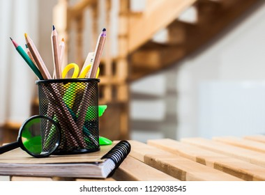 Wire desk tidy full of coloured pencils standing on a wooden table
