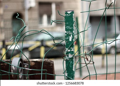 Wire fence green vandalized destroyed city town