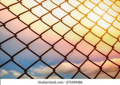 Wire fence or metal net on sunset background, rainbow colorful sky, pastel and vintage style