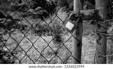 Wire fence with padlock and a white blank sticker - concept - black and white