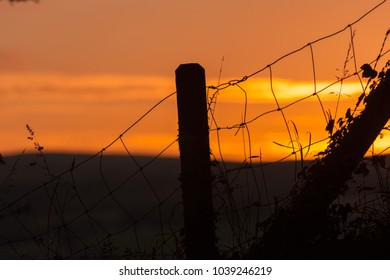 A  wire fence with fence post silhouetted against a red sky at sunset