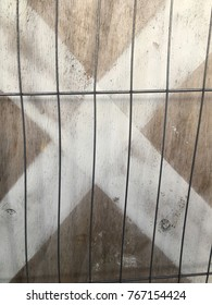 Wire fencing keeping people out with a white X on wooden boarding