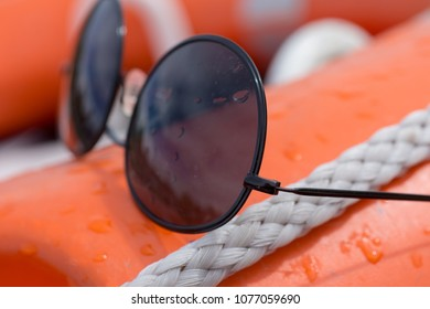 ec37d24a4ce wire frame black sunglasses covered in water droplets placed on board an  orange boat buoyancy aid