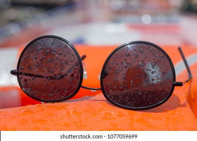 d8cfec204f4 wire frame black sunglasses covered in water droplets resting on board a boat  buoyancy aid