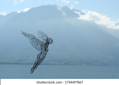 Wire line art angel figurine flying over water through high mountains. Angel woman jumping into the lake wings spread wide open. Open skies with few clouds around the top of the mountain.