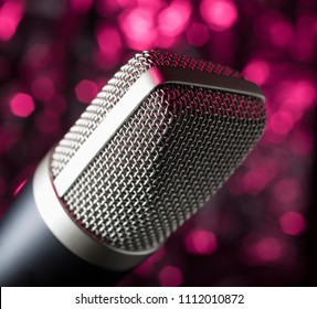 Wire mesh covered microphone on an abstract pink background