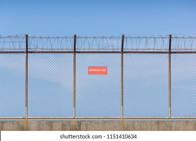 Wire mesh fence and a restricted area sign with blue sky background