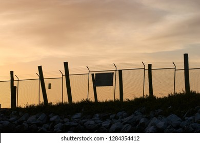 A wire mesh fence, with steel and timber posts; stands in silhouette with an orange/apricot colored sky behind.  Taken at dusk - the maritime wharf facility on Goodwood Island, NSW, Australia.