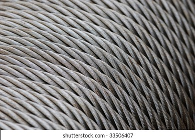 Wire rope texture - heavy duty steel wire cable or rope as background. Coils of wire rope or cable used in the fishing industry. Coil steel wire rope. Close up of steel wire rope cable.