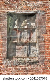 A wire screen covers up a bricked-up window on the outside of a red brick building.