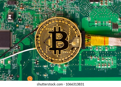Wired bitcoin lying on electronic motherboard of a laptop
