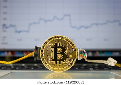 Wired bitcoin on a laptop in front of a price trend graffic on the screen.