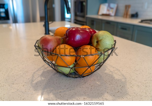 Wired geometric fruit basket with fresh fruits at the kitschen island of home